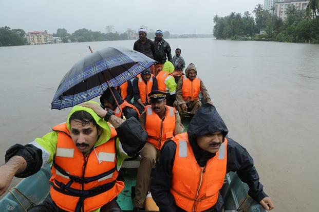 Indian fire and rescue personnel evacuate local residents in an boat flooded following monsoon rains at Aluva, Kerala. Photo:AFP