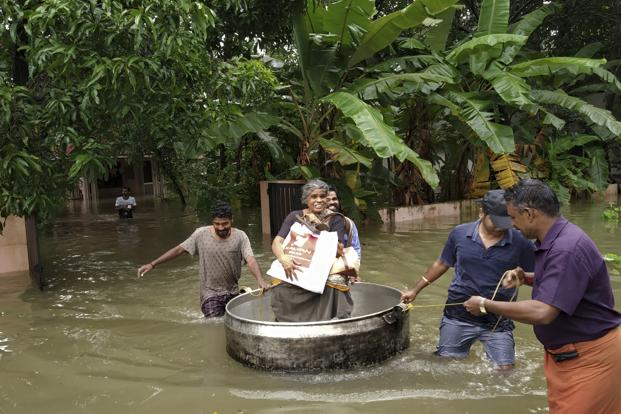 An elderly woman is rescued in a cooking utensil after her home was flooded in Thrissur, Kerala, today. Photo: AP