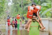 Fire and rescue services personnel carry children through the flood waters in Annamanada village in Thrissur district. Photo: AFP