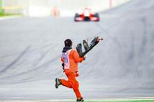 A marshal retrieving debris from the track during the Korean Grand Prix in Yeongam, South Korea, last year. Photo: Clive Mason/Getty Images.