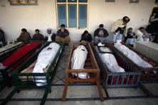 People gather around coffins of victims who were killed by twin explosions. The death toll from a series of bombings in two Pakistani cities on Thursday, one of the bloodiest days in the country's history, has reached 114, police said Friday. Photo: Reuters