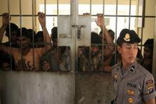 A police officer stands guard near illegal migrants from Myanmar at an immigration detention centre in Medan in Indonesia's North Sumatra province on Friday. Photo: Reuters