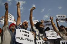 Protesters hold placards and shout slogans as they protest after a Delhi court on Tuesday acquitted a Congress leader, Sajjan Kumar, of charges that he incited mobs to kill Sikhs during 1984 anti-Sikh riots. Photo: AP