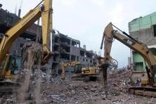 Cranes work to clear rubble from the site of a garment factory that collapsed in Savar, near Dhaka. Photo: AP