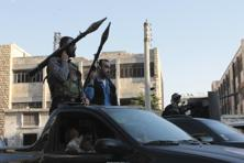 A file photo shows Free Syrian Army fighters holding their weapons while riding on a vehicle before heading to fight in Aleppo's district of Salaheddine. Photo: Reuters