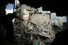 A man looks at a destroyed house, which police said was targeted on Friday in an Israeli air strike, through a hole, in Gaza City 19 July 2014. Photo: Reuters