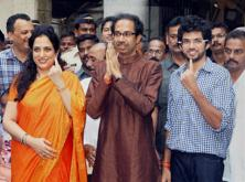 Shiv Sena President Uddhav Thackeray accompanied by wife Rashmi and son Aditya display their inked fingers after casting votes for the Assembly elections in Mumbai on Wednesday. Photo: PTI