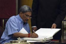 Manohar Parrikar, who resigned on Saturday as the chief minister of Goa, signs after taking oath as a new cabinet minister at the presidential palace in New Delhi. Photo: AP