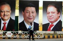 A policeman stands guard next to giant portraits of (L-R) Pakistan's President Mamnoon Hussain, China's President XiJinping, and Pakistan's Prime Minister Nawaz Sharif, displayed along a road ahead of Xi's visit to Islamabad. Photo: Reuters