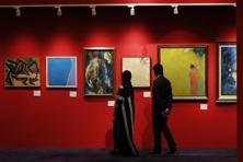 A file photo of visitors look at paintings displayed during an exhibition at Christie's Auction house in Dubai on 15 March 2015. Photo: AFP