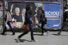 Pedestrians walk past a campaign poster promoting presidential candidate Daniel Scioli, pictured with his wife Karina Rabolini, in Buenos Aires on 23 October. Photo: AP