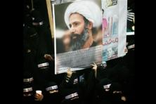 A file photo of a Saudi anti-govt protester carries a poster with the image of Shiite cleric Sheik Nimr al-Nimr. Photo: AP