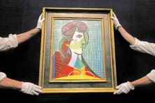 Sotheby's employees hold a painting by Pablo Picasso called Tete de Femme at its auction rooms in London. Auctions of various art genres at Sotheby's, one of the biggest international  auction houses, scheduled for this month are smaller and carry lower estimates than its equivalent event last year. Photo: AP