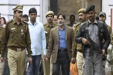 SAR Geelani, former DU lecturer, with Delhi police officers at Parliament street police station in New Delhi on 16 February 2016. Photo: Hindustan Times