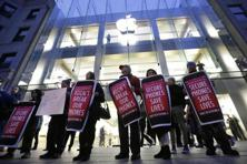 Protesters carry placards outside an Apple store in Boston. Law enforcement groups asked to support the government, saying their ability to extract data from evidence is critical to solving crimes and protecting the public. Photo: AP