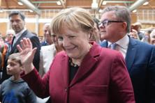 German chancellor Angela Merkel waves next to Guido Wolf, the top candidate of the Christian Democratic Union for state elections in federal state Baden-Wuerttemberg. Photo: AFP