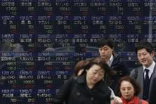 A file photo of an stock board showing Japan's stock prices in Tokyo. Japan's biggest trading companies expect to book combined writedowns of at least $8.6 billion. Photo: AP
