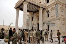 In this photo released on 24 March, 2016, by the Syrian official news agency SANA, Syrian government soldiers gather outside a damaged palace, in Palmyra, central Syria. Photo: AP/PTI