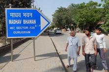 People move past a board bearing address of RSS office in Gurgaon on Thursday. Photo: PTI