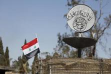 A file photo shows a Syrian national flag fluttering next to the Islamic State's slogan at a roundabout where executions were carried out by ISIS militants in the city of Palmyra. Photo: Reuters