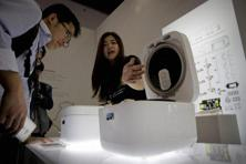 An exhibitor introduces a rice cooker to a visitor at a display booth for Mijia, a new brand of Xiaomi at the 2016 Global Mobile Internet Conference. Photo: AP/PTI
