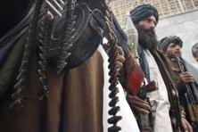 Taliban militants hold their heavy and light weapons during a ceremony. Photo: Fraidoon Pooyaa/AP