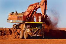 A file photo shows a digger loading ore onto a dump truck. Iron ore has been on a wild ride in 2016 following three years of losses spurred by rising low-cost production. Photo: Bloomberg