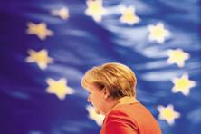 German Chancellor Angela Merkel walks past a flag of Europe. Photo: Johannes Eisele/AFP