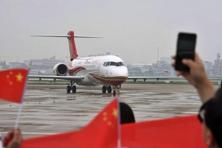 People wave flags and take photos as a Chengdu Airlines ARJ21-700 regional jet taxis after landing at the Hongqiao Airport in Shanghai, China. Photo: AP