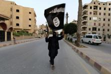 A Islamic State member in Iraq and the Levant (ISIL) waves an ISIL flag in Raqqa. Photo: Reuters