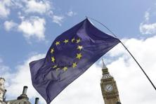 A European Union flag is held in front of the Big Ben clock tower in Parliament Square in London. Photo: Reuters