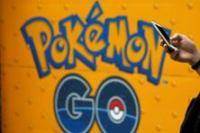A man uses a mobile phone in front of an advertisement board bearing the image of Pokemon Go at an electronic shop in Tokyo, Japan. Photo: Reuters