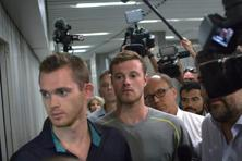 Journalists surround American Olympic swimmers Gunnar Bentz, left, and Jack Conger, center, as they leave the police station at Rio International airport. Photo: AP