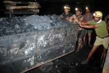 Indian coal miners push a trolley laden with coal inside an underground tunnel of a mine owned by SCCL at Godavarikhani, 250 km east of Hyderabad. Photo: AFP