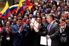 Senate President Mauricio Lizcano receiving from Colombia's President Juan Manuel Santos, front right, the peace deal with rebels of the Revolutionary Armed Forces of Colombia, FARC, in Bogota, Colombia, Thursday. Photo: AP