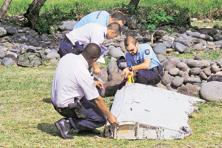Investigators inspect a large piece of plane debris found on a beach in Saint-Andre, on the French Indian Ocean island of La Reunion, on 29 July 2015. Photo: Reuters