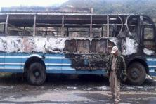 A policeman walks in front of a charred bus burnt down by bandh supporters of United Naga Council, at Senapati, Manipur on Monday. Photo: PTI