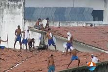 The TV grab shows that prisoners throwing objects from the prison roof during a riot in Brazil that killed 26 inmates. Photo: AFP