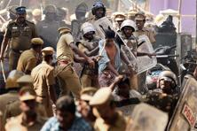 Police charged a crowd of thousands with canes and burst tear gas shells to disperse protesters at Marina beach in Chennai on Monday. Photo: PTI