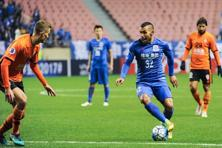Carlos Tevez of Shanghai Shenhua (right) challenges Daniel Bowles of Brisbane Roar in a qualifying match during the 2017 AFC Champions League in Shanghai on 8 February. Photo: AFP