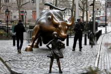 A cameraman films a statue of a girl facing the Wall Street Bull in New York. Photo: Reuters