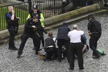 A policeman points a gun at a man on the floor as emergency services attend the terror attack scene in Westminster. The UK Parliament attack and the Westminster Bridge car rampage left five dead and at least 40 injured. Photo: AP