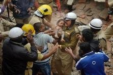 A child being recused after a building collapsed due to a suspected cylinder blast at Ejipura in Bengaluru on Monday. PTI