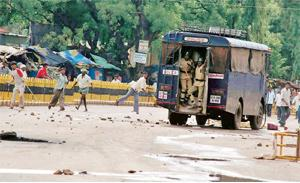 Snowballing crisis: Angry farmers throw stones at a police wagon during a protest on Tuesday against the authorities in Karnataka, demanding fertilizers and seeds.