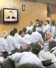What next: Pakistani lawyers in Lahore listen as Pervez Musharraf, in his last televised appearance as president on Monday, announces his resignation, ending an eight-year tenure. Photograph: KM Chaud