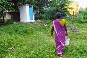 A woman using the toilet constructed by Hyundai in Irungattukottai village.