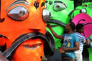 An artist giving final touches to the effigies of Ravan. PTI.