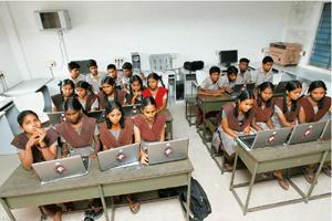 Early beneficiaries: Students with their laptops at a higher secondary school in Tamil Nadu. J. Jayalalithaa's administration intends to give away 6.8 million laptops to students of government-aided h