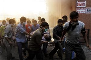 People evacuate patients after a fire broke out at a nursing home in Kolkata on 9 December 2011. AP