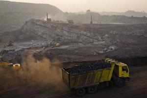 A fully laden truck carrying coal drives out of an open-cast coal mine as excavation work continues in the village of Jina Gora, near Jharia. Daniel Berehulak /Getty Images